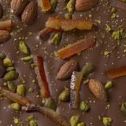 Chocolat au lait aux amandes, pistaches et oranges confites